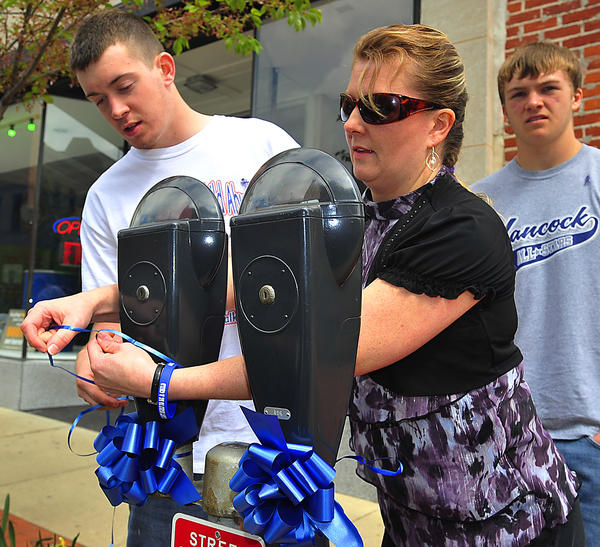 Lorie Faith, center, ties blue ribbons to downtown Hagerstown parking meters Sunday with help from Garrett Wiles. Skylar Faith watches. An event to kick off Child Abuse Prevention Month in April was held at University Plaza. Blue ribbons are symbols of the effort.