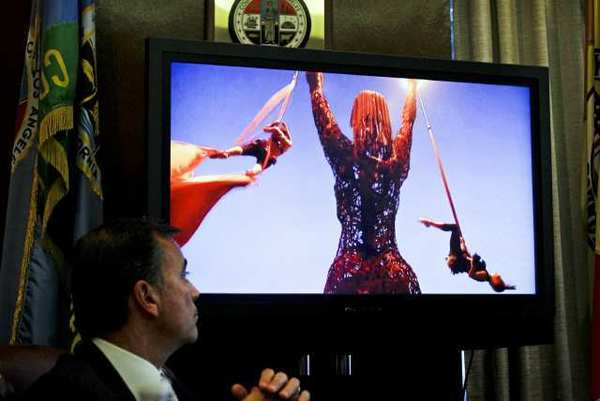Developer Rick Caruso, a Coliseum commissioner, watches images of a rave at a meeting of the Coliseum Commission.