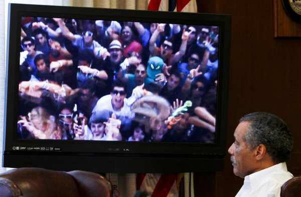 Los Angeles city councilman Bernard Parks at a meeting of the Coliseum Commission in February 2011, looking at a photo of the Electric Daisy Carnival rave the previous summer.