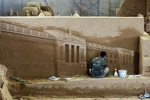Jooheng Tan, a sculptor from Singapore, finishes a sand replica of Buckingham Palace.
