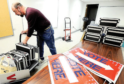 Larry Shipe, an election clerk, loads electronic poll books and printers on a rolling cart Monday afternoon at the Washington County Board of Elections in downtown Hagerstown.