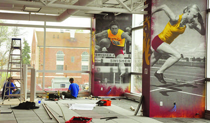 Darby Feist, left, and Jeff Woolridge of Aberdeen, both with Hayes Plumbing and Heating, work on the second floor of the Barnett Center. Floor-to-ceiling portraits of Northern State University athletes run the length of the north side. American News Photo by Anita Meyer