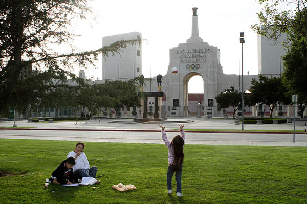 Crishell Calvillo, 5, plays catch with herself as her grandmother Leticia Calvillo, helps her cousin Anthony Gomez, 7, do his homework, near the Los Angeles Memorial Coliseum, seen in background on March 5, 2012.