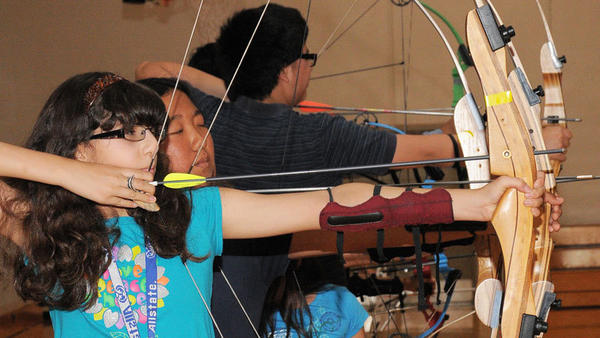 Alejandra Guzman draws her bow and lines up her shot during archery practice held at Ryerson Youth Center on Aug. 12 in El Centro.
