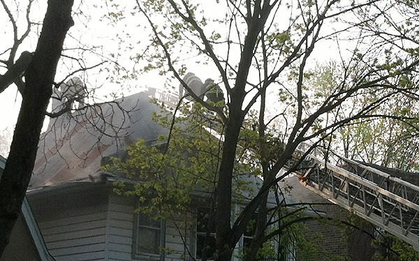 Firefighters work on the roof of a home in the 6500 block of Newgard Avenue in Rogers Park this morning.