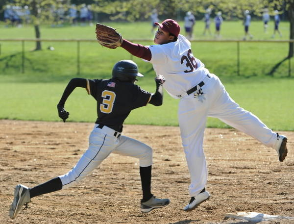 St. Frances' Correlius Boykins, left, makes it to first base when Dunbar's Dandre Mitchell misses the ball. St. Frances beat Dunbar, 15-2, in President's Cup.