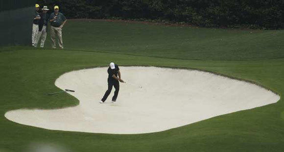 Tiger Woods hits out of a sand trap during a practice round at the Masters.