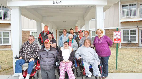 The Alpine Haus residents who lost their homes in the 2009 fire are finally home. Here, posing before the entry of the new Alpine Haus are residents (front row, l-r): Tim Smith, Allen Beemus, Monica Kessler, Stacey Miller, Andrea Rolla; (middle row, l-r): Kyle Russell, Dorothy Sumerau, Audrey Bonnell; (back row, l-r): Charles Park, Penny Briley, Ray Chiffen, Dave Russell, William Rowe.