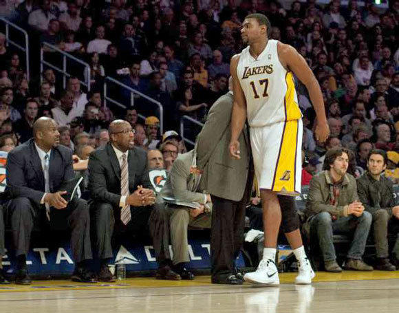 Andrew Bynum limps to the bench after injuring his ankle.