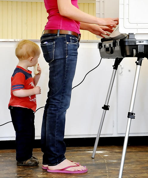 James Monore of Ringgold eats a sandwich while his mom, Barbie Barvir, casts her vote at the Ringgold Ruritan Building on Tuesday.