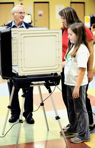 Peggy Mothershed, 10, helps her mom, Hope Mothershed, cast her vote Tuesday evening at Maugansville Elementary School. Answering Hope's questions is Voting Unit Judge Jay Stouffer.