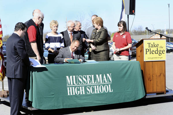 W.Va. Gov. Earl Ray Tomblin visits Musselman High School in Inwood Tuesday to sign legislation outlawing texting while driving in the state.