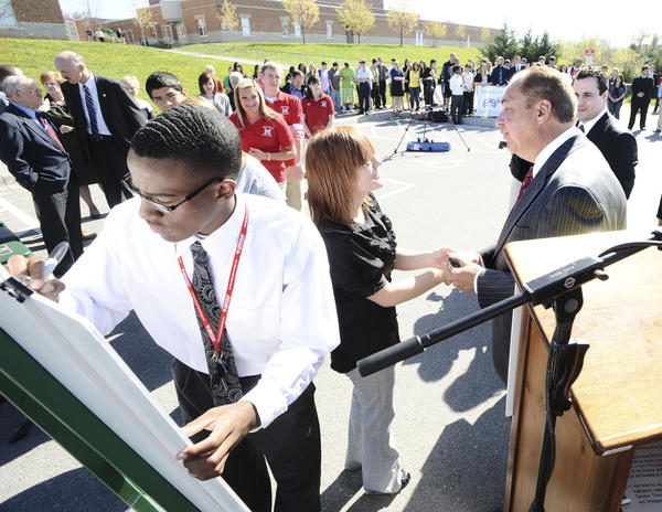 Mussleman High School junior Joshua Ferguson, left, signs West Virginia Gov. Earl Ray Tomblin's Safe Driver Pledge at the school in Inwood Tuesday while Tomblin, right, shakes hands with students who already took the pledge.