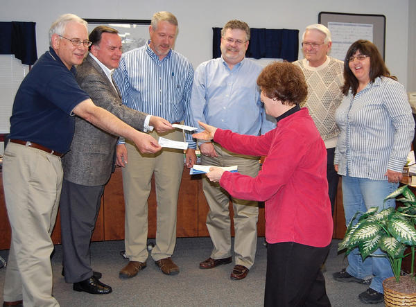 Washington Township, Pa., secretary Karen Hargrave collects checks Monday from the township supervisors and manager. Each person made a donationto the Sept. 11, 2001, memorial planned at Red Run Park. From left are Township Manager Mike Christopher, and supervisors William Conrad, Jeff Geesaman, Stephen Kulla, Dick McCracken and Elaine Gladhill.
