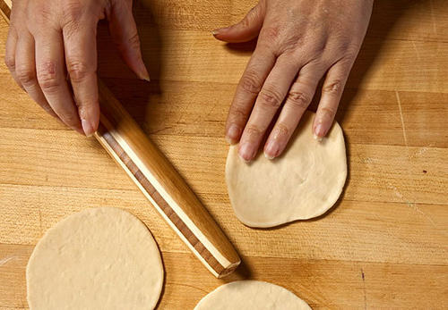 <b>Roll:</b> Take a golf ball-sized piece of the dough and roll it out into a small, thin circle about 4 inches in diameter on a lightly floured surface.