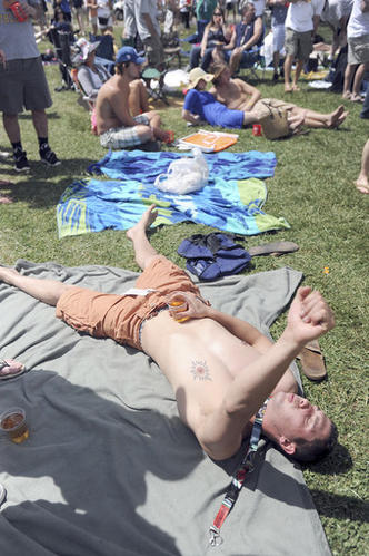 With drink in hand, Terry Smith cheers on the bikini contest while laying on his back in the Preakness infield around 10:30 a.m.