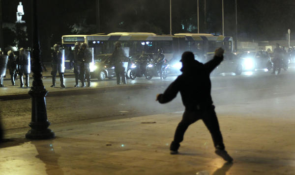 A man hurls rocks at riot police outside the Parliament today in Athens.