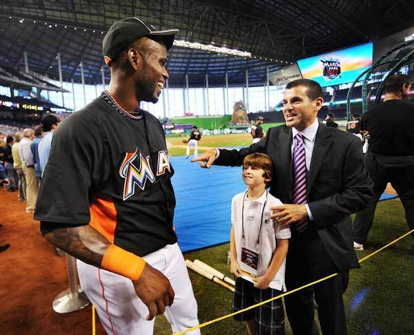 Marlin's shortstop Jose Reyes smiles as he talks with team president David Samson and his son.