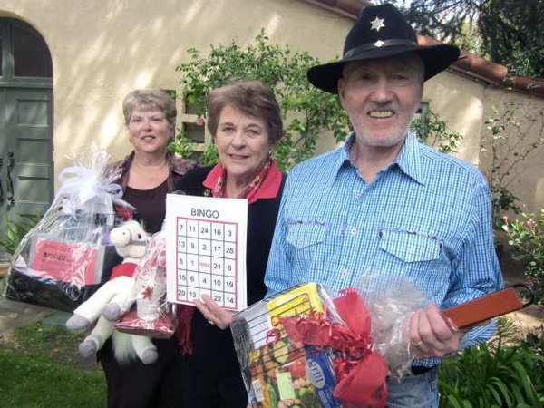 Corkie MacPherson, from left, chairman of the upcoming BBQ Bingo fundraiser for the La Ca-ada Flintridge Tournament of Roses Assn., shows some of the prize packages with Association President Ann Neilson and Daryal Gant, who will serve as emcee for the April 28 event.