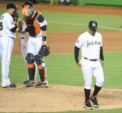 Ozzie Guillen walks off the mound on Opening Night after meeting with his pitcher.
