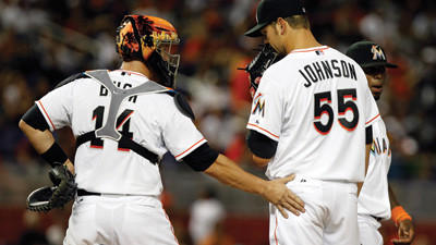 Miami Marlins catcher John Buck (14) talks with starting pitcher Josh Johnson (55) in the sixth inning during the Opening Day baseball game against the St. Louis Cardinals, Wednesday