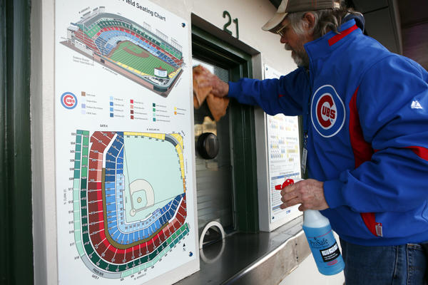 Grounds worker John Kelly cleans the ticket window glass outside Wrigley Field early Thursday before the Cubs' afternoon season opener against the Nationals.