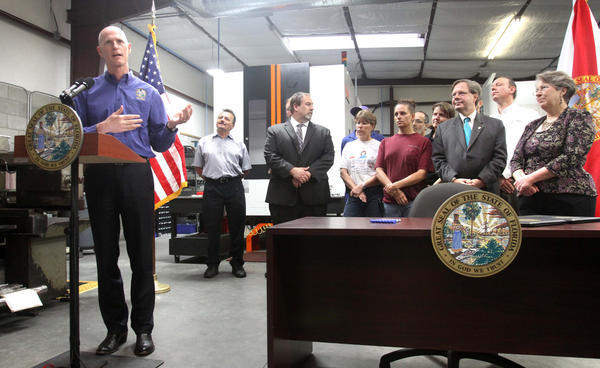 Gov. Rick Scott addresses employees of Metal Essence, a precision-metal and plastics fabrications company in Longwood, during a bill-signing ceremony for a series of tax cuts and incentives, and the return of a three-day,  back-to-school sales tax holiday, Thursday, April 5, 2012.