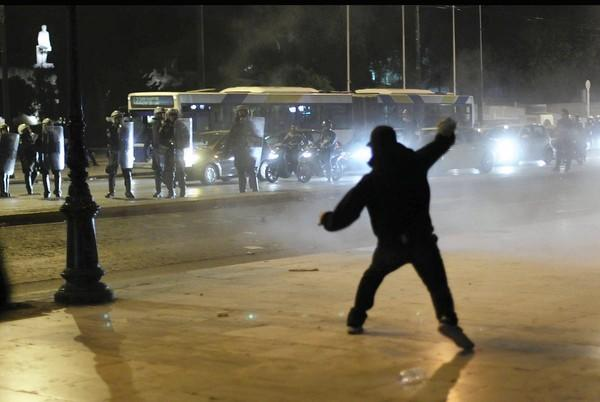A man hurls rocks at riot police outside the Parliament in Athens.