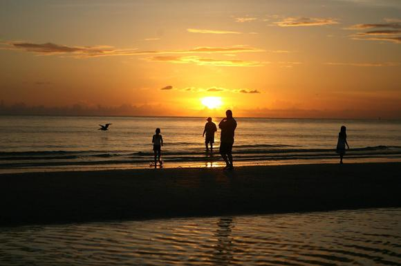 People walk as children play on the beach during sunset July 16, 2007 in Marco Island, Florida.
