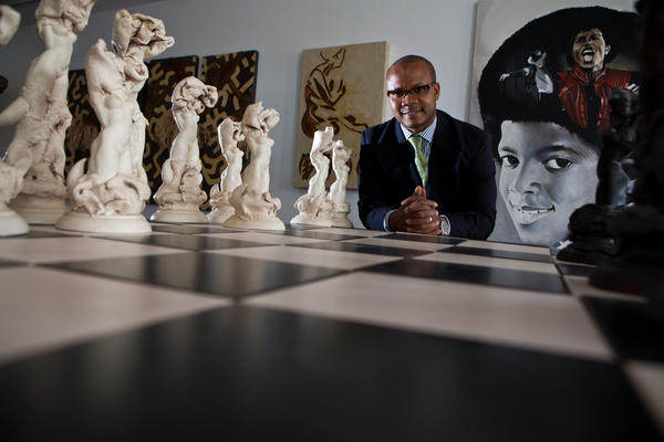 Andre Guichard, owner of Gallery Guichard in Bronzeville neighborhood of Chicago on Thursday, March 29, 2012. The art includes, Pedro Pulido, ceramic chess set, front, and Shawn Warren, oil on canvas, back.