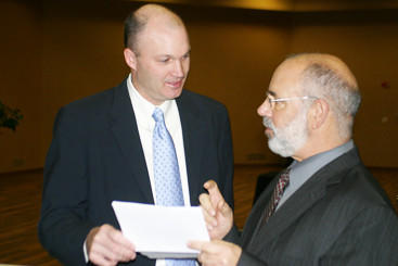 Professional tennis player David Wheaton, left, goes over the program for the Community Prayer Breakfast with Don Peck, master of ceremonies, on Thursday.