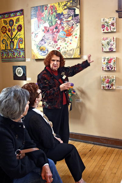 "Jordan River Art Center board member Raechel Alberts discusses art works with art patrons during the opening of the ""Florescence"" show in the East Jordan gallery."