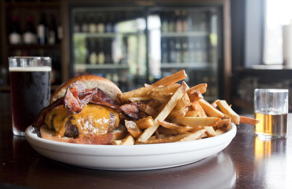 Bacon-topped burger with fries at Longman & Eagle