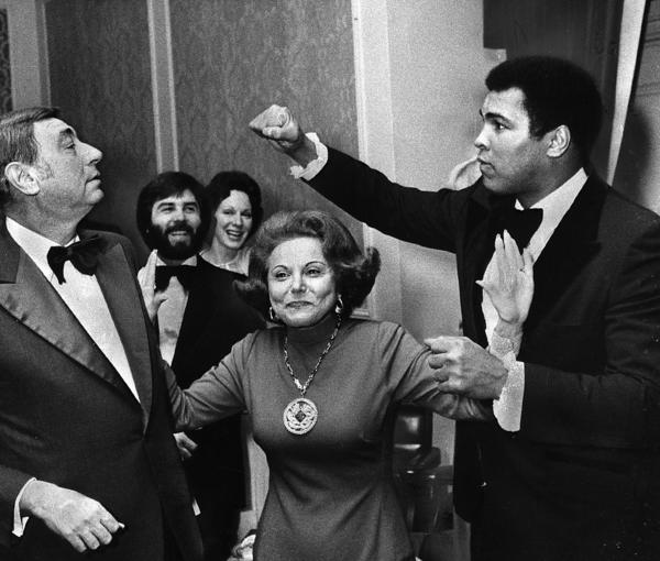 "At a dinner honoring the six ""outstanding Chicagoans of today"", Muhammad Ali takes a playful poke at sportscaster Howard Cosell. Advising them to break clean is columnist Ann Landers, Nov. 11, 1977, at the Palmer House in Chicago."