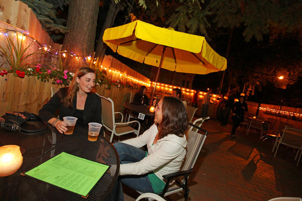 The fenced-in backyard patio at Marble features umbrellas, lights and flower-filled planters.