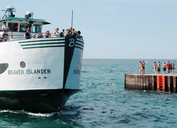 "A group of young people swim off the end of the Pine River Channel's north pier as the Beaver Islander makes its way into the channel last summer. Although the swimmers pictured here are not technically in violation of the current ""no swimming"" ordinance, they would be in violation of the proposed revised ordinance."