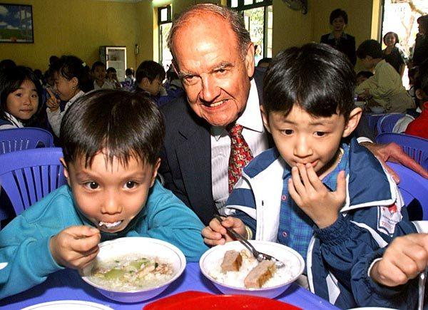 George McGovern, U.S. ambassador to the U.N. Food and Agricultural Agency, visits with children during their lunch break at the Trung Tu Primary School in Hanoi, Vietnam, in March 2001. McGovern was visiting Vietnam to meet with government officials and international organizations to discuss developing a global Food for Education Initiative.
