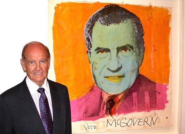 "Former Sen. George McGovern poses in front of an Andy Warhol painting of Richard Nixon titled ""Vote McGovern"" during a visit to Los Angeles' Museum of Contemporary Art in 2008."