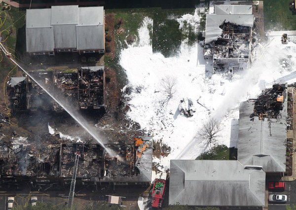 Emergency crews extinguish a fire at the scene of a jet crash Friday, April 6, 2012 in Virginia Beach, Va.