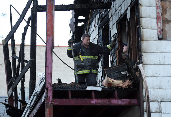 Chicago firefighters investigate where a body was found at the scene of an an earlier fire in the 1600 block of N. Mozart on Friday, April 6, 2012.