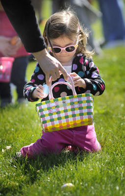 In the Emmaus Egg Hunt sponsored by the Emmaus Kiwanis Club Carolina Snyder, 2, of Emmaus places eggs she has found into a basket held by her mother Krista Snyder of Emmaus. The annual event is held in Emmaus Community Park.