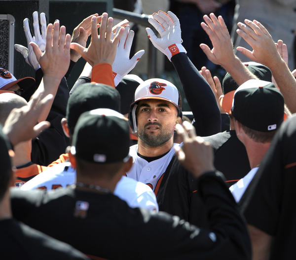 The Baltimore Orioles' Nick Markakis receives the congratulations of his teammates after his two-run home run in the first inning against the Minnesota Twins. The Orioles defeated the Twins on Opening Day at Camden Yards.