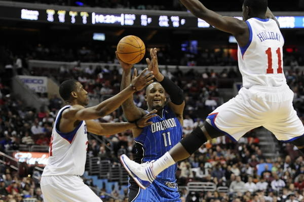 Orlando Magic forward Glen Davis (11) passes the ball under pressure from Philadelphia 76ers forward Thaddeus Young (21) and guard Jrue Holiday (11) during the fourth quarter at the Wells Fargo Center. The Magic defeated the Sixers 88-82 on Saturday, April 7, 2012.