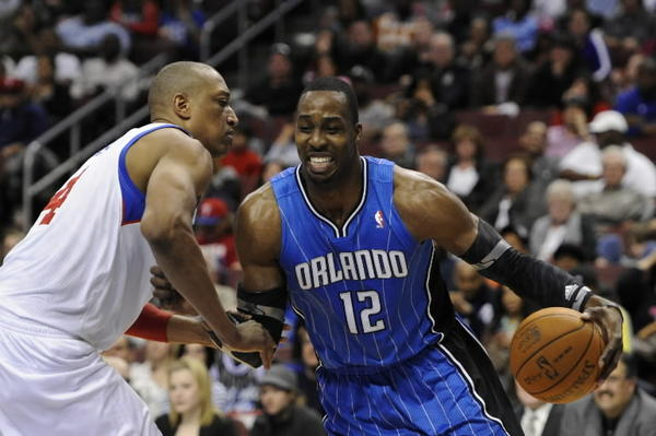 Orlando Magic center Dwight Howard (12) is defended by Philadelphia 76ers center Tony Battie (4) during the second quarter at the Wells Fargo Center. The Magic defeated the Sixers 88-82 on Saturday, April 7, 2012.