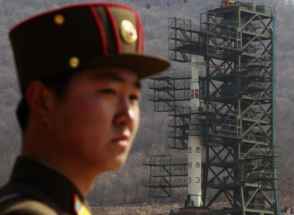A soldier stands guard in front of the Unha-3 (Milky Way 3) rocket sitting on a launch pad at the West Sea Satellite Launch Site, during a guided media tour by North Korean authorities in the northwest of Pyongyang.