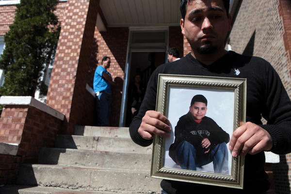 Erik Lopez holds the photograph of his half brother, thirteen-year-old Adrian Luna, on Sunday. Adrian was shot and killed last night sitting on the steps of this home on the 4600 block of South Spaulding Avenue.