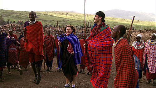 "Engaged couple Rachel (center) and Brendon (right) jump with the Masai warriors on ""The Amazing Race."""