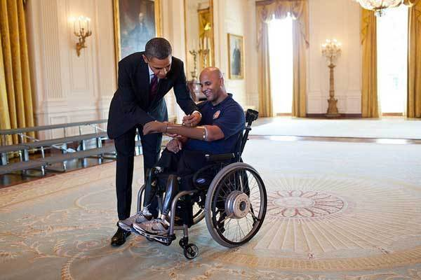 President Barack Obama signs the prosthetic arm of Sgt. Carlos Evans, USMC, after greeting wounded warriors in the East Room during their tour of the White House, March 6, 2012. First Lady Michelle Obama first met Evans, who was injured in Afghanistan while on his fourth combat deployment, during a visit to Walter Reed Army Medical Center in 2010.