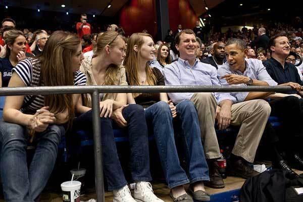 President Barack Obama talks with students during game one of the NCAA Men's Basketball Tournament ¿First Four¿ at the University of Dayton Arena in Dayton, Ohio, March 13, 2012. The President watched Mississippi Valley State take on Western Kentucky with Prime Minister David Cameron of the United Kingdom, right, and Trip Director Marvin Nicholson, center.