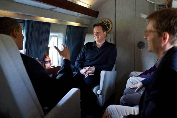 President Barack Obama talks with Prime Minister David Cameron of the United Kingdom aboard Marine One en route to Joint Base Andrews, Md., before traveling on to Dayton, Ohio, March 13, 2012. Press Secretary Jay Carney is seated at right.